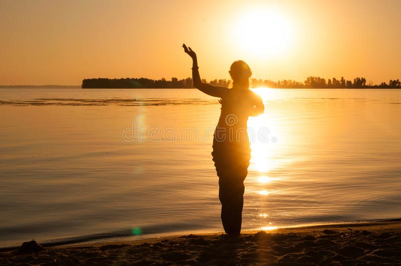 tradición de baile oriental trible de la mujer cerca de la costa grande del río en el amanecer fotografía de archivo