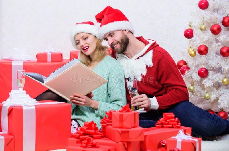 Tradición de la familia Champán de la bebida de la abrazo de la familia cerca del árbol de navidad mientras que mira el álbum de  fotografía de archivo libre de regalías