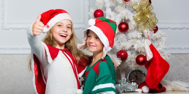 Tradición del día de fiesta de la familia Los niños alegres celebran la Navidad Trajes santa de la Navidad de los niños y duende  fotografía de archivo