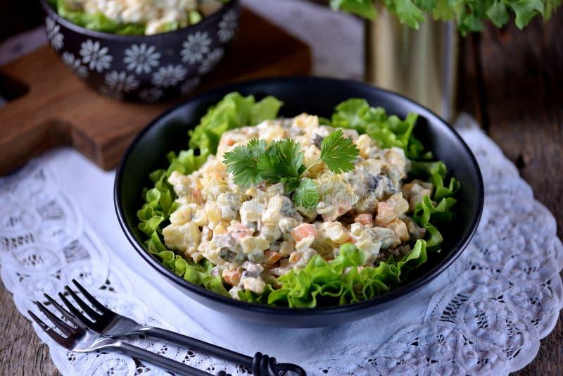 ` Tradicional de Olivier do ` da ensalada russa com batatas, salmouras, ovos, cenoura e maionese imagens de stock royalty free