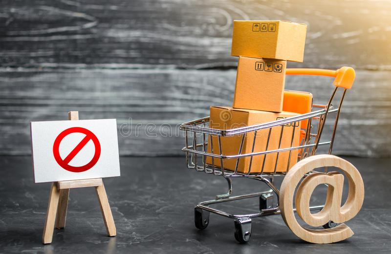 Trading cart with boxes and an easel with a prohibition symbol NO. Internet trade online shopping ban. Restriction on importation. Goods, proprietary for royalty free stock image