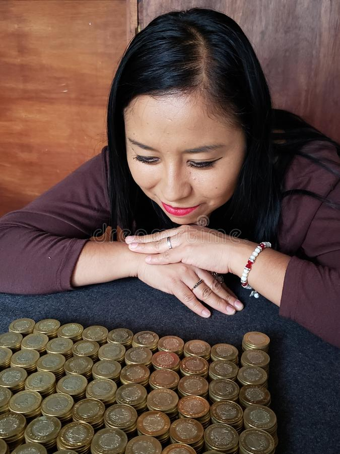 brunette business woman looking stacked mexican coins royalty free stock photos