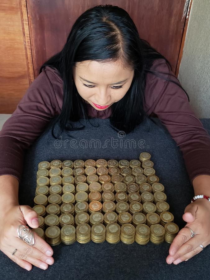 brunette business woman holding stacked mexican coins royalty free stock photography
