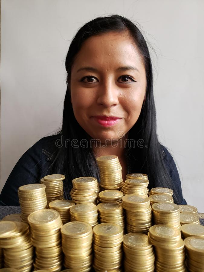 brunette business woman and stacked mexican coins royalty free stock image