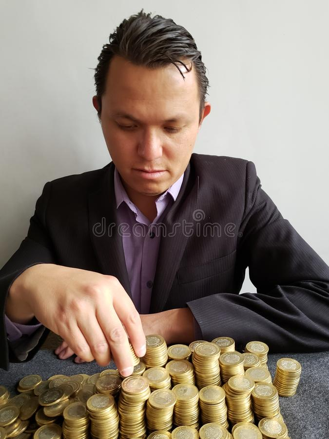 Economic growth, young businessman stacking mexican coins of ten pesos. Trading and exchange, bank and commerce, price of buy and sell, cash value and money royalty free stock images