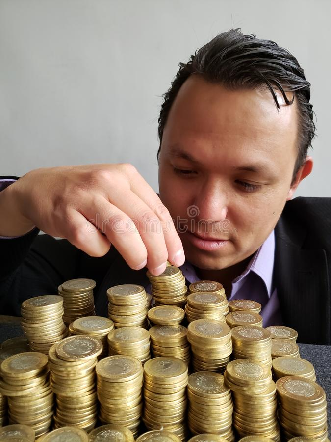 Economic growth, young businessman stacking mexican coins of ten pesos. Trading and exchange, bank and commerce, price of buy and sell, cash value and money royalty free stock photography