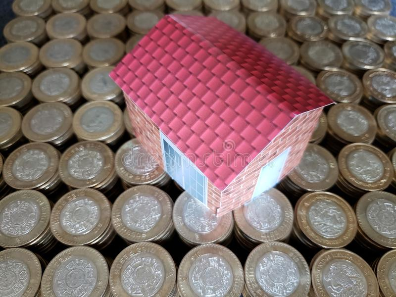 figure of a house and coins of ten mexican pesos stock images