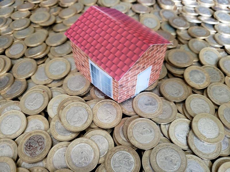 figure of a house and coins of ten mexican pesos stock photos