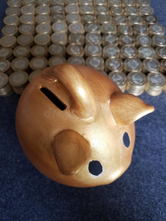 Golden pig piggy bank and stacked coins of mexican pesos. Trading and exchange, bank and commerce, price of buy and sell, cash value and money, economy and stock image