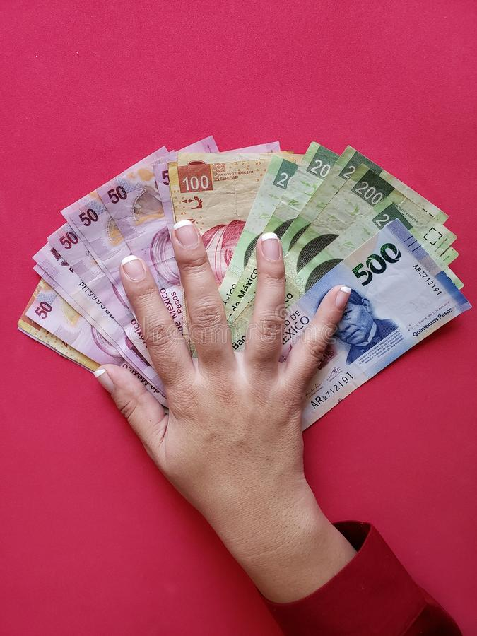 hand of a businesswoman holding mexican banknotes royalty free stock photography