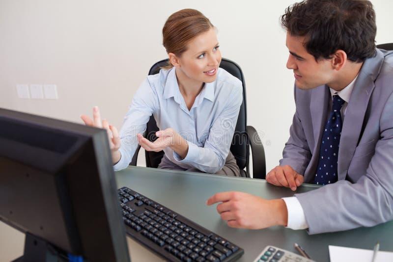 Download Trading Partner Sitting Behind A Desk While Talking Stock Image - Image: 22221577