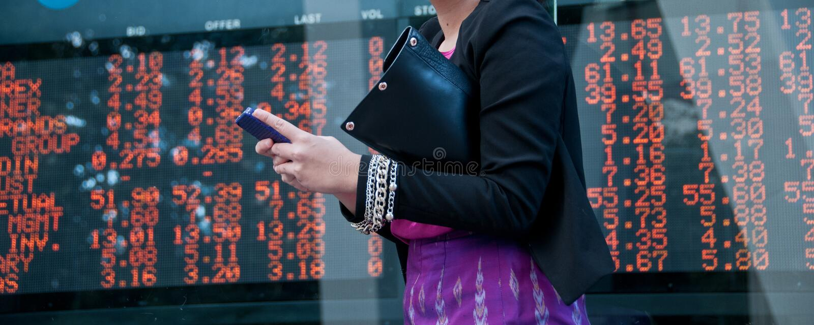 Trading stock on mobile near exchange board stock images
