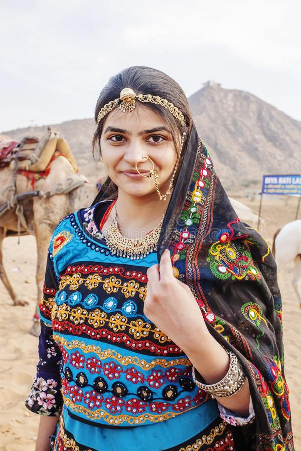 Traditinally dressed young Indian woman with camels and vehicle at Pushkar desert stock photography