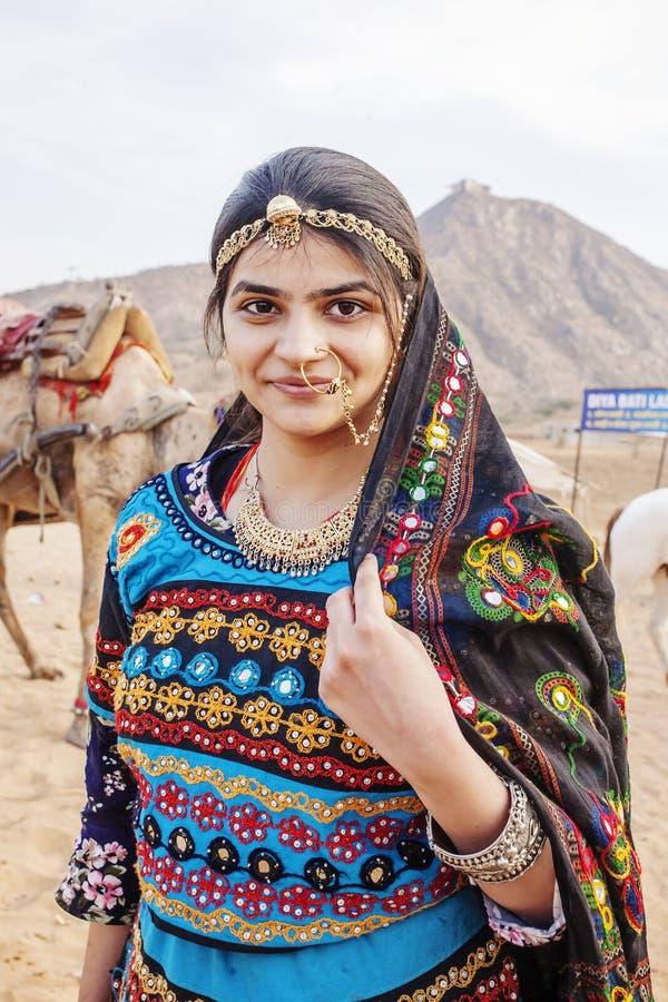 Traditinally ha vestito la giovane donna indiana con i cammelli ed il veicolo al deserto di Pushkar fotografia stock