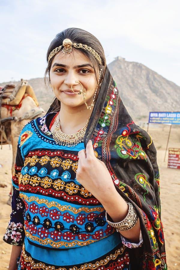 Traditinally klädde den unga indiska kvinnan med kamel och medlet på den Pushkar öknen royaltyfria foton