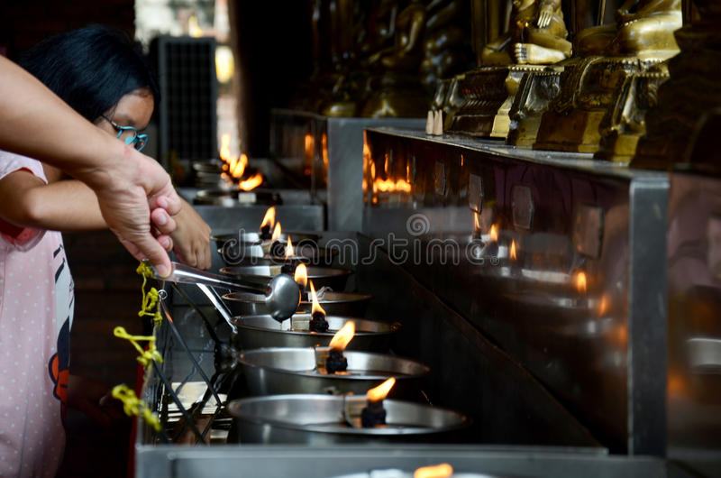 Tradition and culture of thailand, Thai people offering oil lamp. S to fill in the lamp of birthday at Wat Yai chaimongkol in Ayutthaya, Thailand royalty free stock images