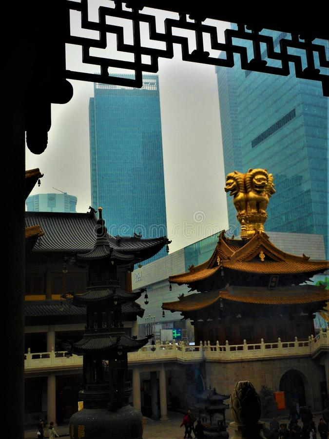 Tradition and modernity in China, temple and skyscrapers, religion and luxury. Golde and progress, development and contrasts, altitude and elevation royalty free stock images