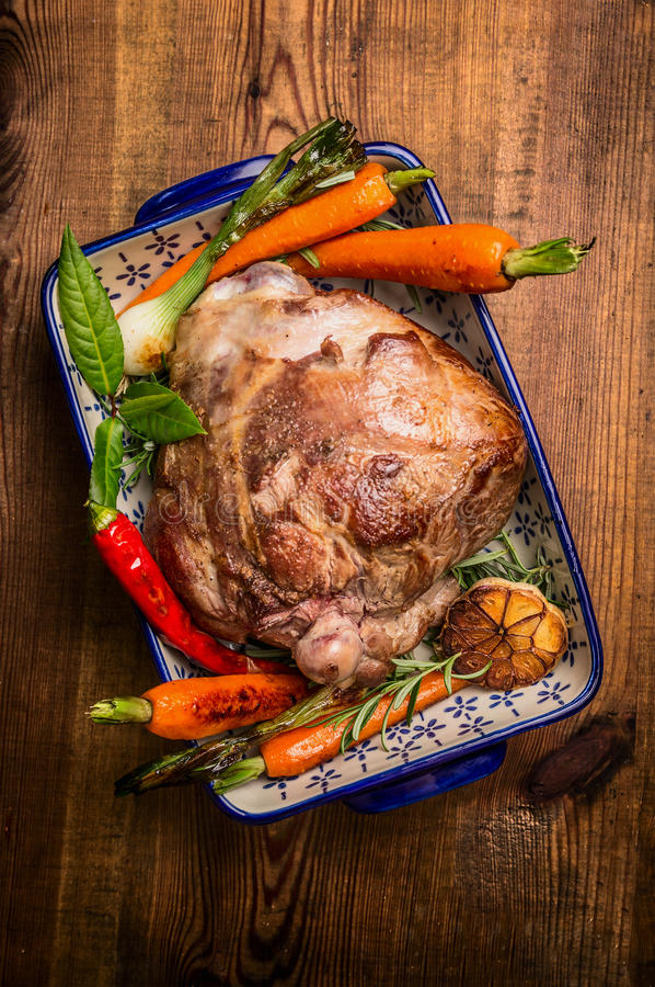 Tradition roasted lamb leg with carrot and fresh herbs in rustic bowl on wooden background stock photography