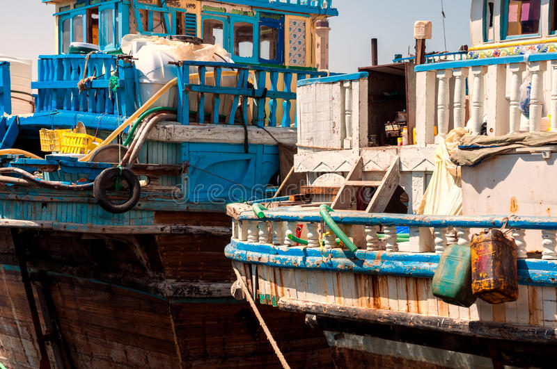 Traditional Abra taxi boats in Dubai creek - Deira, Dubai Deira, United Arab Emirates. Traditional wooden dhows boats in Dubai creek district dock during busy stock photo