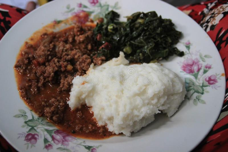 Traditional African cuisine for poor people - cornmeal porridge Maize or Ishim with spinach. And meat stock photography