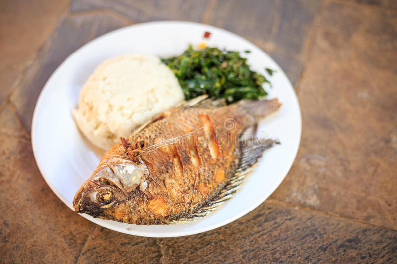 Traditional african food - ugali, fish and greens. Traditional East African food - ugali, fish and greens in Kenya royalty free stock photography