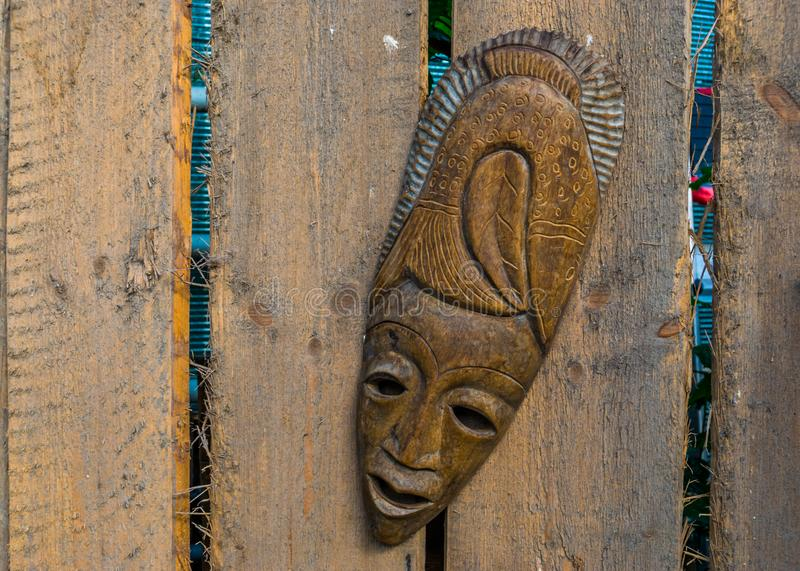 Traditional african mask hanging on a wooden fence, tropical garden decorations, native background royalty free stock photo
