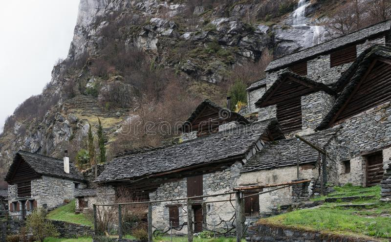 Traditional alpine village with many small wooden and stone houses and a mountain waterfall backdrop stock photo