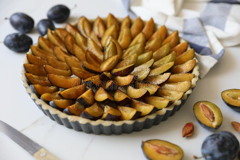 Traditional Alsatian Plum tart French: Tarte aux quetsches alsacienne . Top view. Top view of delicious Traditional Alsatian Plum tart French: Tarte aux stock photo