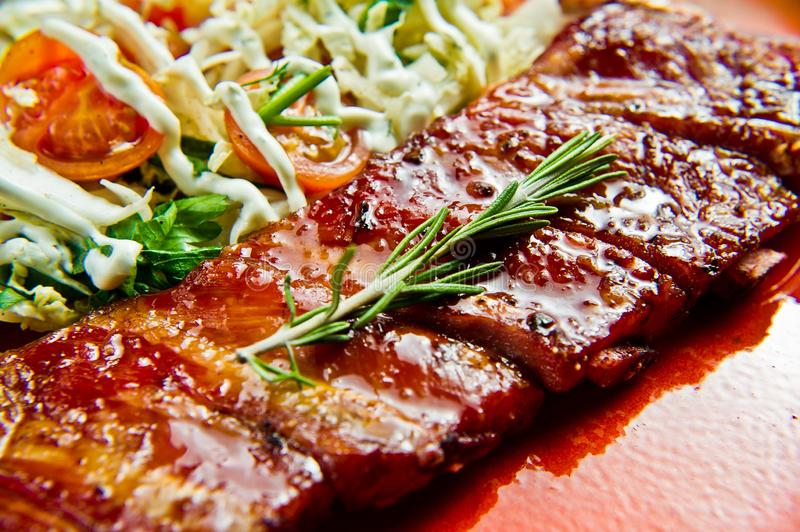Traditional American barbecue pork ribs with a side dish of green salad. Gray background, side view, close-up. stock image