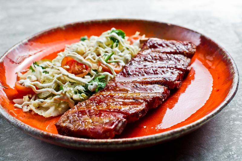 Traditional American barbecue pork ribs with a side dish of green salad. Grey background stock photos