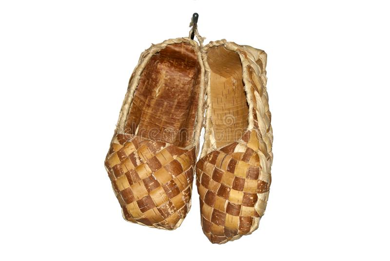 Traditional ancient woven bast shoes hanging on the wall isolated. Traditional ancient woven bast shoes, fiber taken from the bark of trees, hanging on the wall royalty free stock images