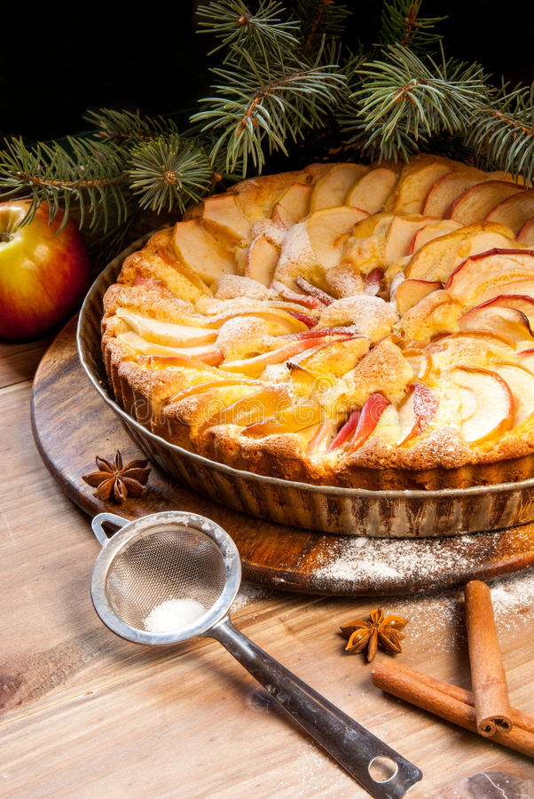 Traditional apple pie and Christmas tree branches. Traditional apple pie on a wooden table, with apple and powdered sugar. Near the Christmas tree branches royalty free stock image