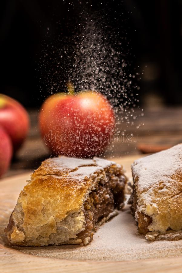 Traditional apple strudel with powdered sugar on wooden rustic background stock image