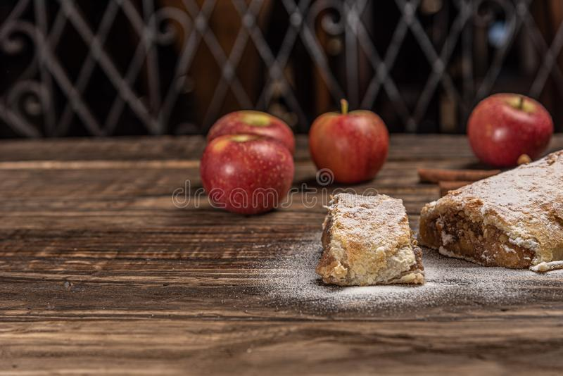 Traditional apple strudel with powdered sugar on wooden rustic background royalty free stock photography
