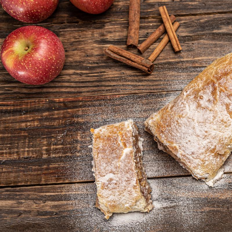 Traditional apple strudel with powdered sugar on wooden rustic background stock photography