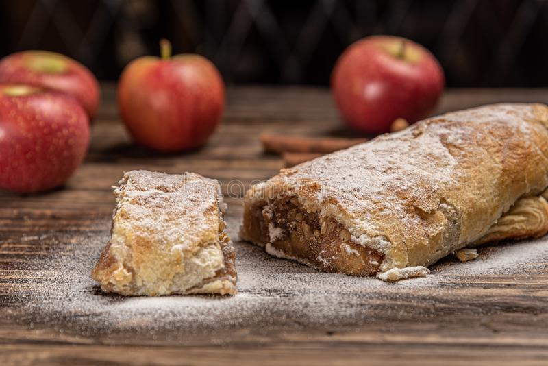 Traditional apple strudel with powdered sugar on wooden rustic background stock photos