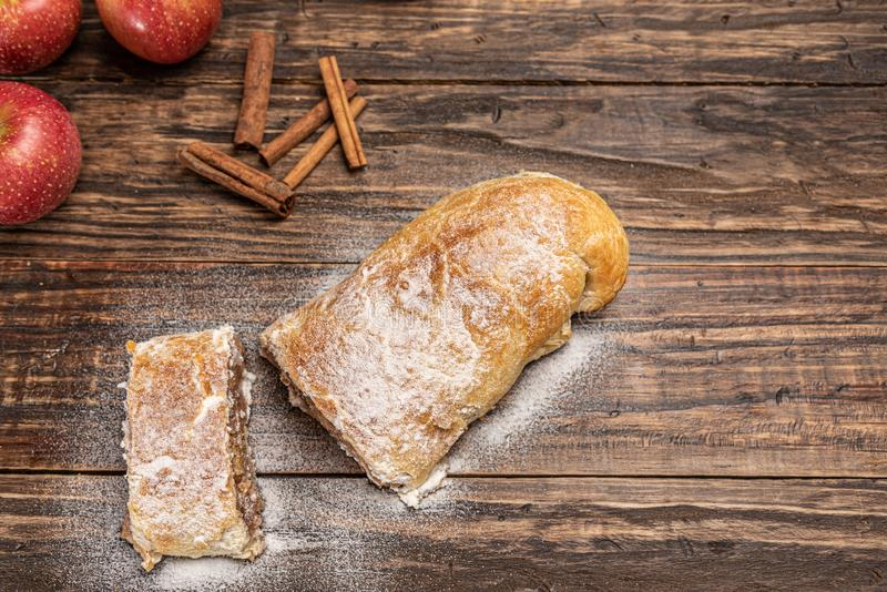 Traditional apple strudel with powdered sugar on wooden rustic background stock images