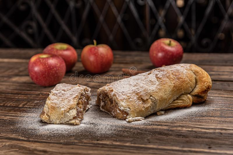 Traditional apple strudel with powdered sugar on wooden rustic background royalty free stock photo