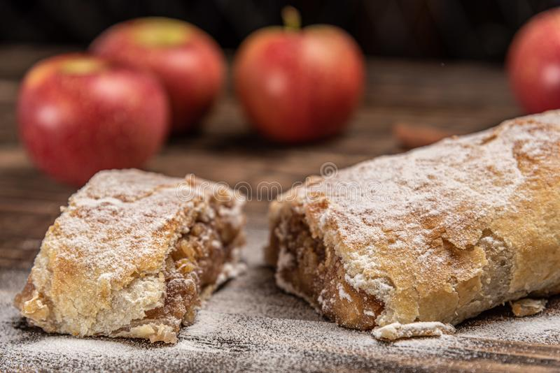 Traditional apple strudel with powdered sugar on wooden rustic background royalty free stock images