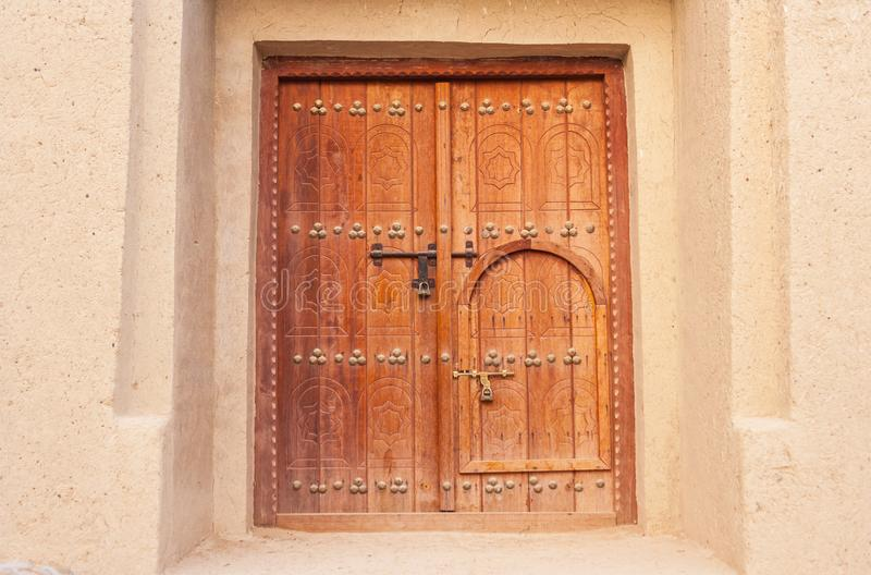 Traditional Arabian `Door Within a Door`. A traditional Arabian `door within a door` in a building in in Al Ain, in the emirate of Abu Dhabi, United Arab stock image