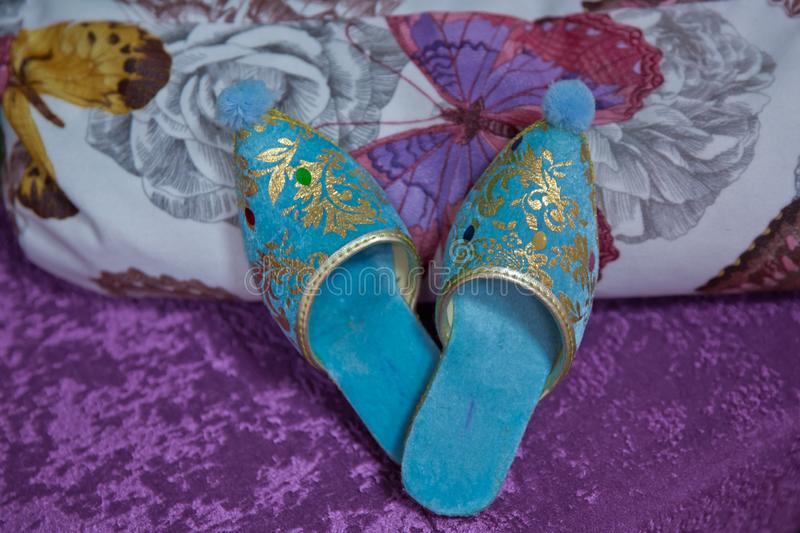 Traditional Arabic blue shoes . Arabian oriental blue shoes in the Aladdin style . on white beech. pink background . Arabian stock photography