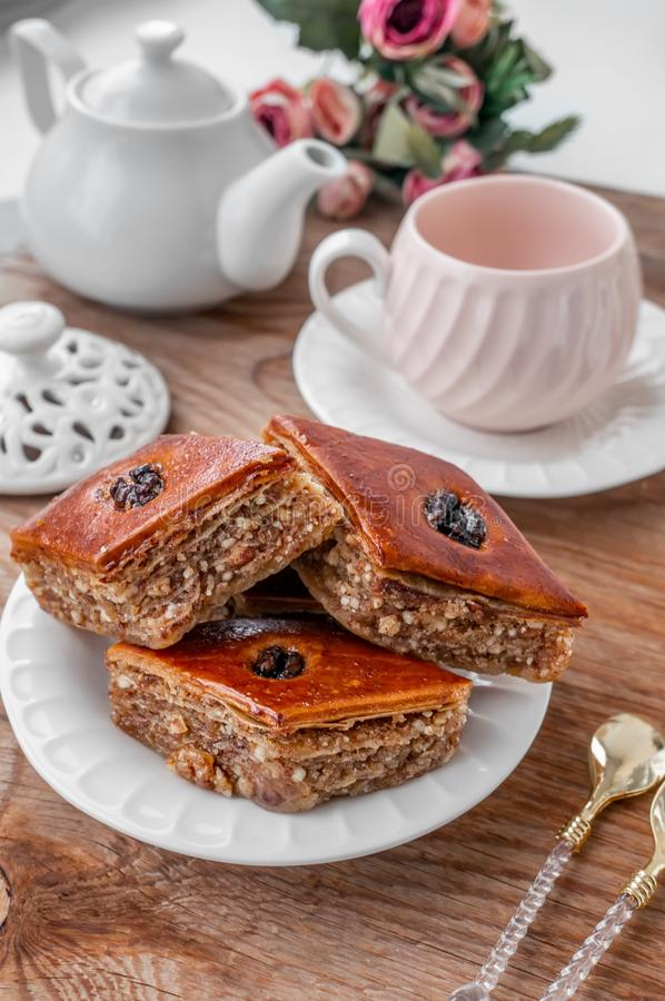 Traditional arabic dessert baklava with a cup of coffee, cashews, walnuts and cardamom on a wooden table. Homemade Baklava with royalty free stock images