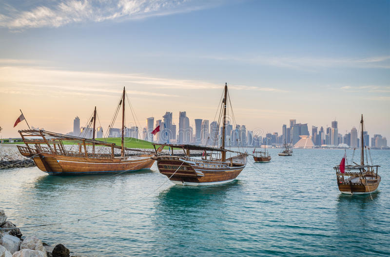 Traditional arabic dhows in Doha, Qatar. Traditional wooden dhows moored off Museum Park, Doha, Qatar, with the city's postmodern 21st Century high-rise skyline stock photos
