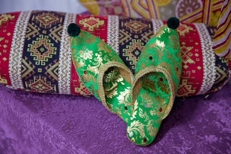 Traditional Arabic green shoes . Arabian oriental green shoes in the Aladdin style . on red beech. pink background . Arabian royalty free stock photos