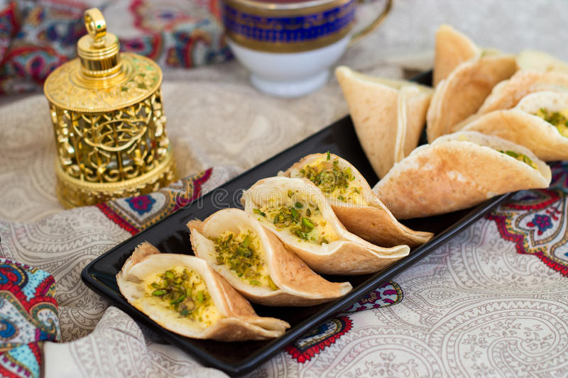 Traditional Arabic kataif crepes stuffed with cream and pistachios, prepared for iftar in Ramadan, oud in gold, on paisley stock photography