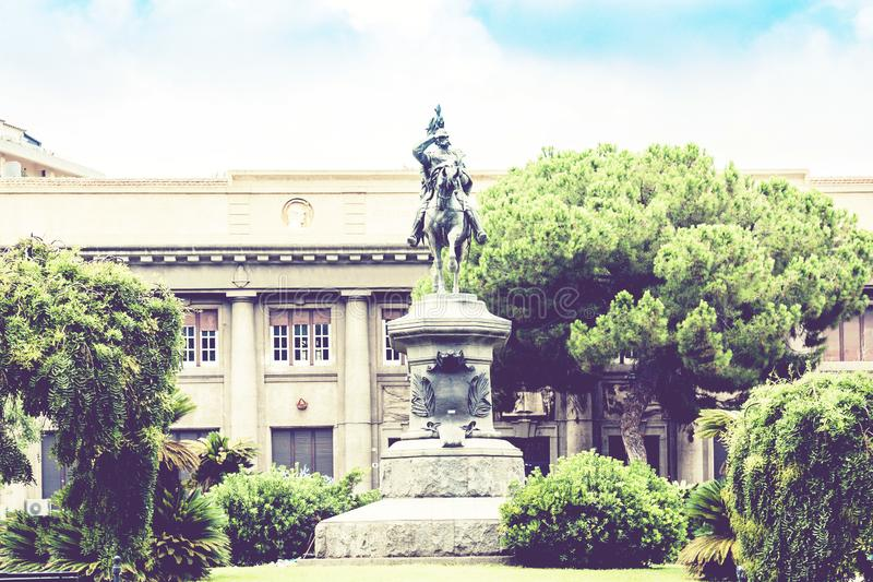 Traditional architecture of Sicily in Italy, typical street of Catania, tree alley, facade of old buildings with monument of King. Re Umberto royalty free stock images
