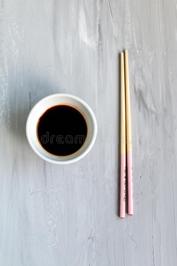 Traditional asian cutlery with plate, bowl for soy sauce bamboo sticks. Concept. With space for text. Grey background royalty free stock photo