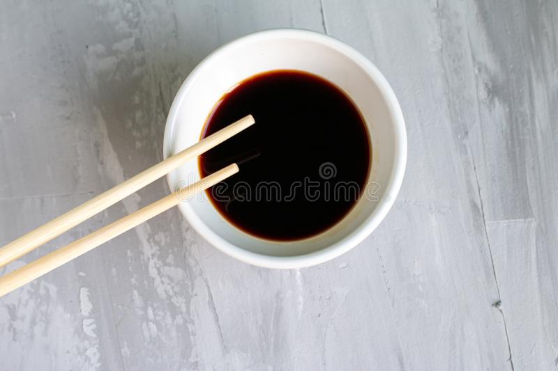 Traditional asian cutlery with plate, bowl for soy sauce bamboo sticks. Concept. With space for text. Grey background royalty free stock image