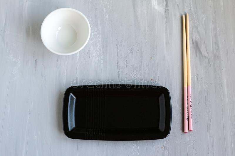 Traditional asian cutlery with plate, bowl for soy sauce bamboo sticks. Concept. With space for text. Grey background stock photo