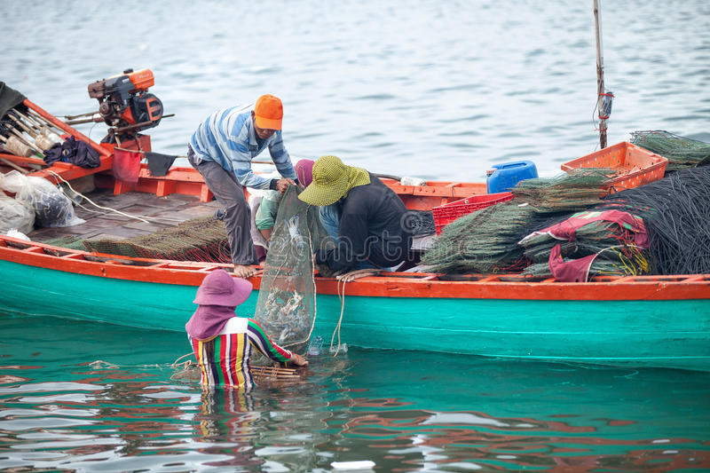 Traditional asian fishing. KEP PROVINCE, CAMBODIA- DECEMBER 2014: Traditional asian fishing. Cambodian men on the fishing boat pass the catch of blue crabs to stock photo